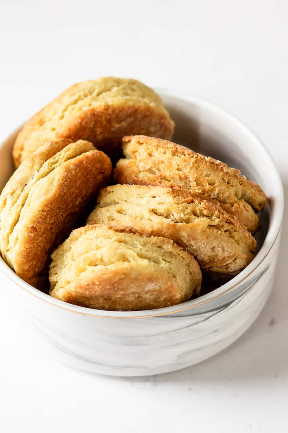 A white bowl filled with five vegan biscuits. Three of them are in a row and two are to the left and all of the biscuits are on their side. The bowl is on a white counter.