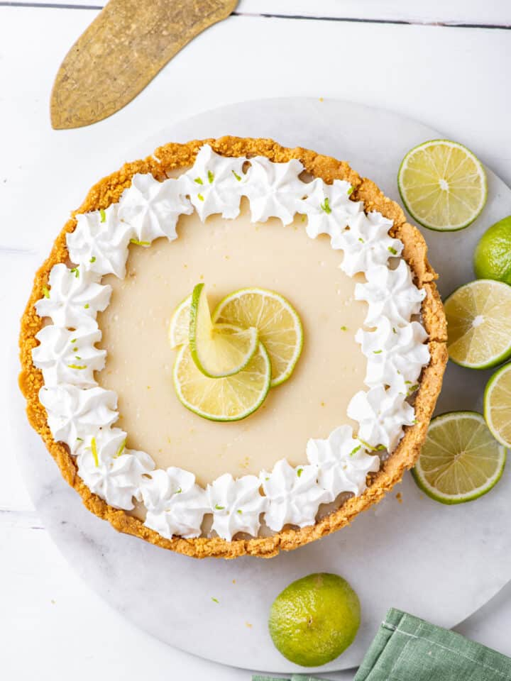 An overhead view of a whole vegan key lime pie. The pie is on a circular white marble board with limes at the right edge of it. The marble board is on a white counter.