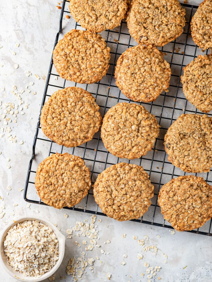 An overhead view of three rows of four vegan oatmeal cookies sitting on a black wire rack. A small white bowl of oats is set in front of the wire rack, with a few oats on scattered on the white counter everything is sitting on.