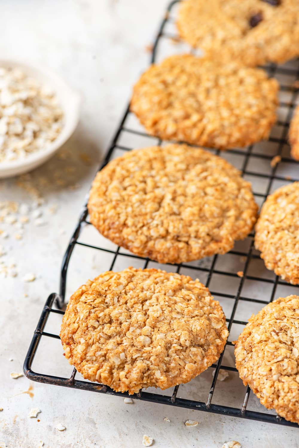 A row of four vegan oatmeal cookies lined up on a black wire rack. A small white bowl of oats is to the left of the wire rack. Everything is set on a white counter.