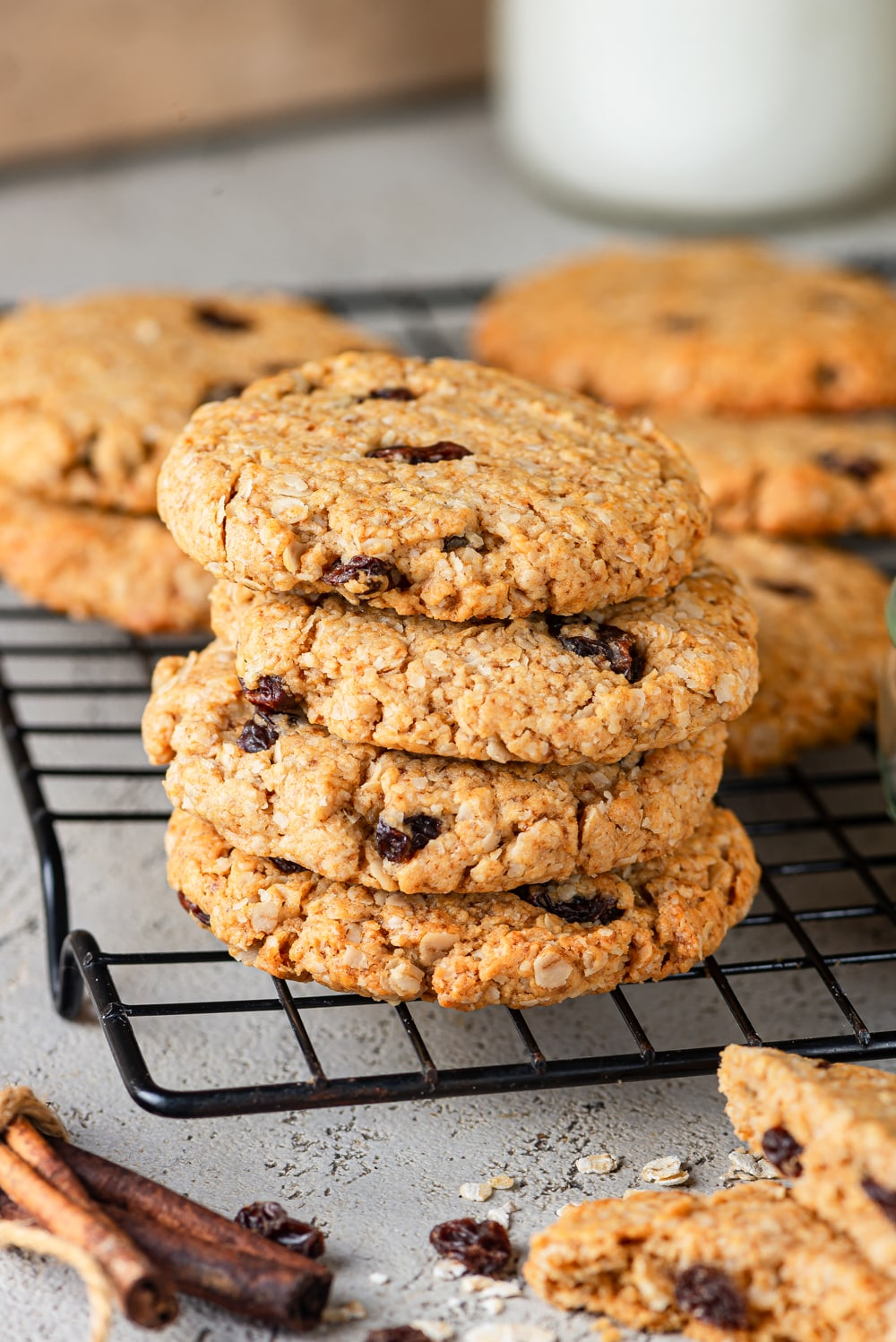 A stack of four vegan oatmeal raisin cookies on a wire rack, with five cookies set behind the stack. A bundle of cinnamon and broken in half cookies are in front of the rack and everything is set on a grey counter.
