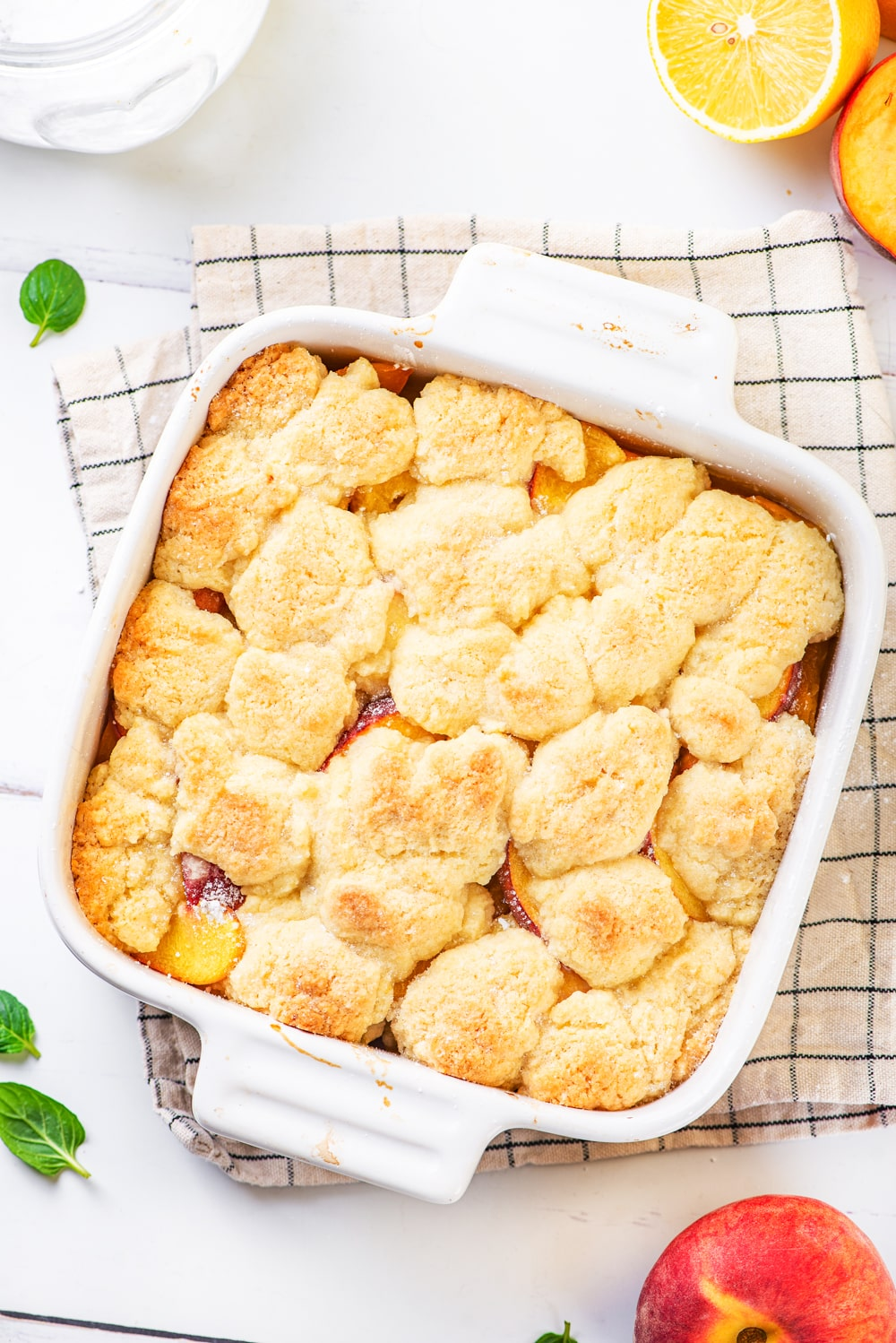 Vegan peach cobbler in a white baking dish on a white and blue plaid tablecloth. The tablecloth is on a white counter.
