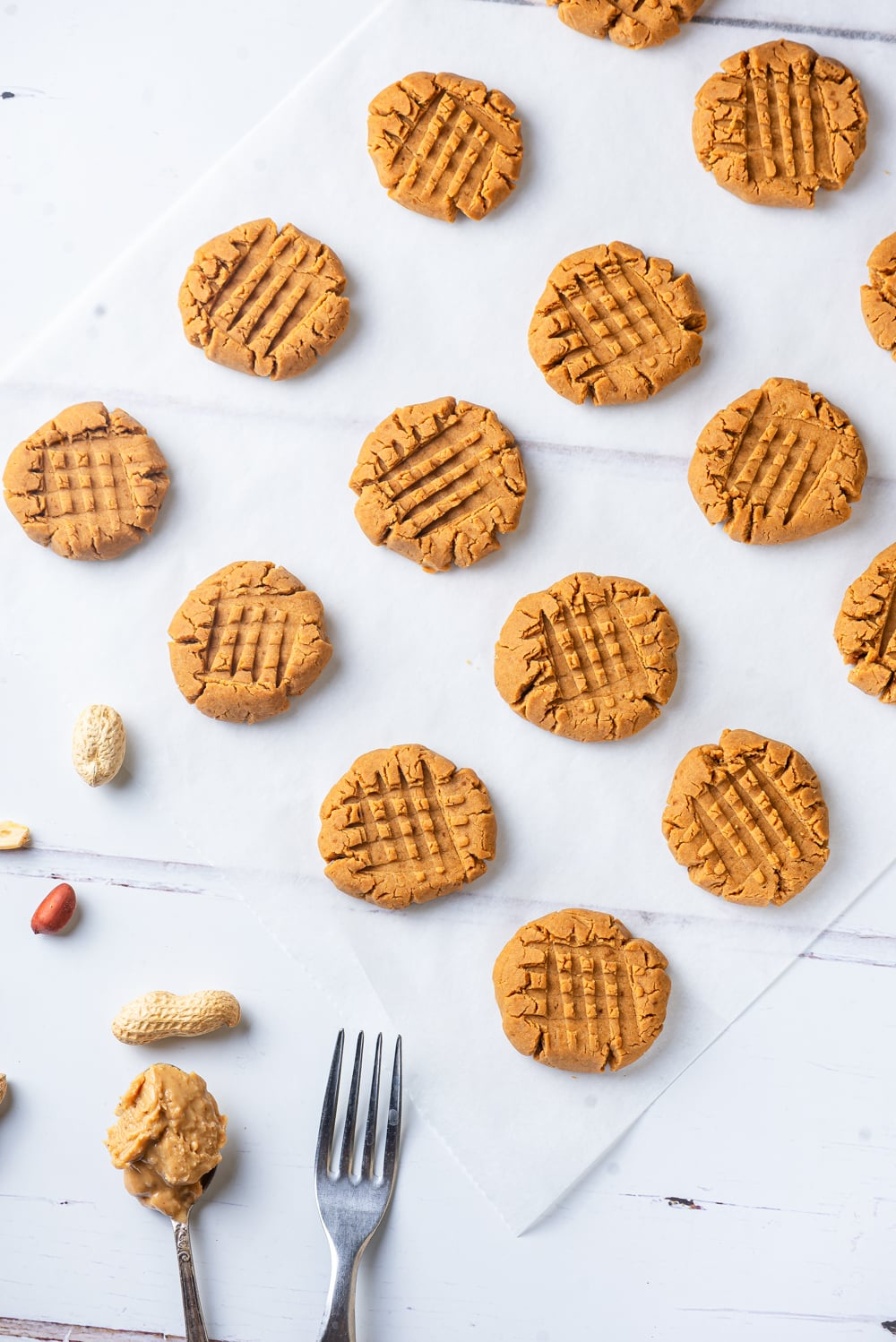 An overhead diagonal view of four rows of four vegan peanut butter cookies lined up with one another. There is a spoonful of peanut butter and a fork at the bottom left of the cookies.