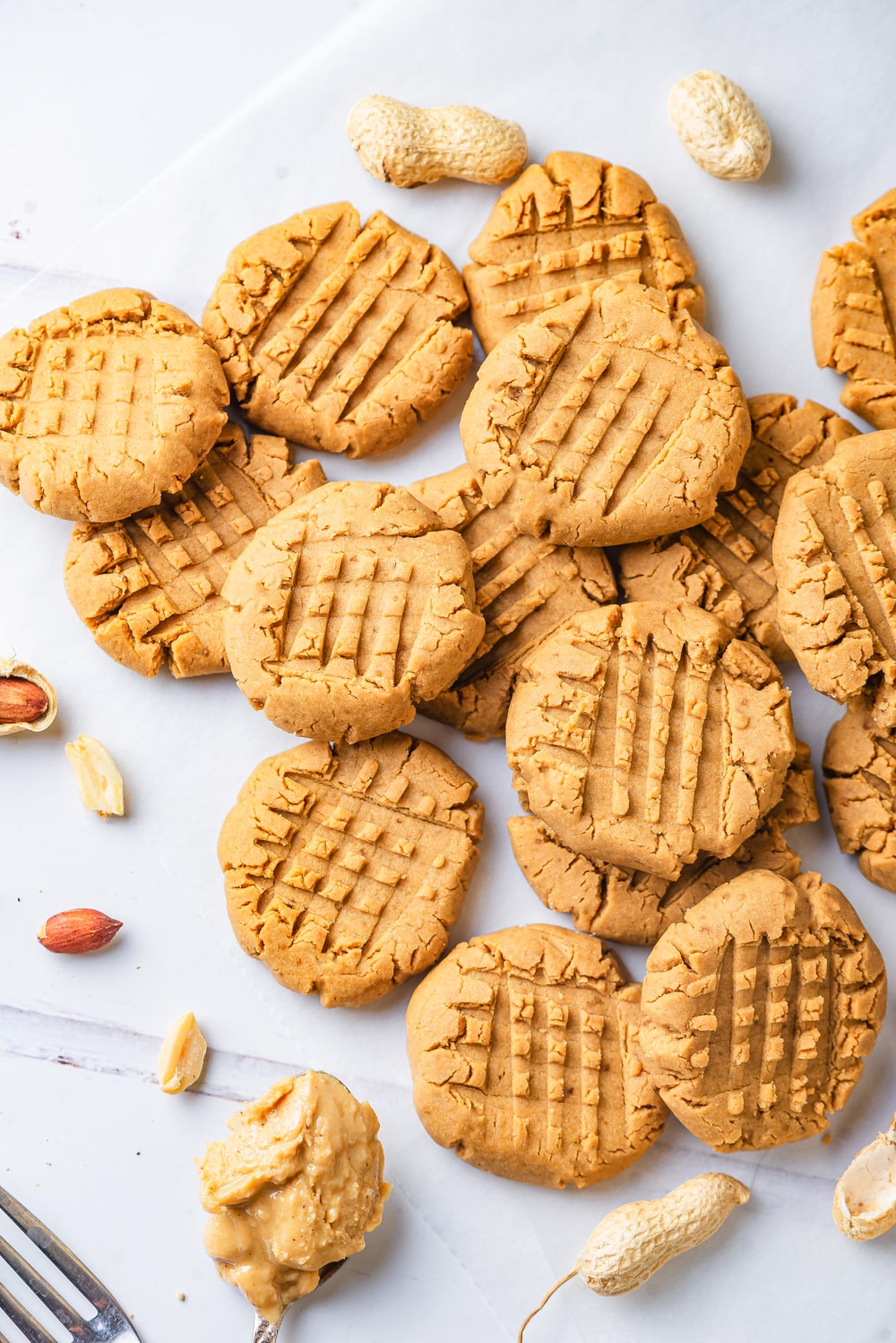 About fourteen vegan peanut butter cookies scattered on a white counter. Some cookies are laying flat and others are overlapping one another. There is a spoonful of peanut butter at the bottom of all the cookies and few peanuts scattered on the outsides of the group of cookies.