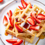 An overhead view of three square vegan waffles unevenly stacked on top of each other with maple syrup and cut up strawberries on them. The waffles are on white plate and there are a few pieces of strawberries on the plate as well. A gold fork is at the front of the plate with the tip of the prongs hidden by the top waffle. The plate is on a tablecloth on a white counter.