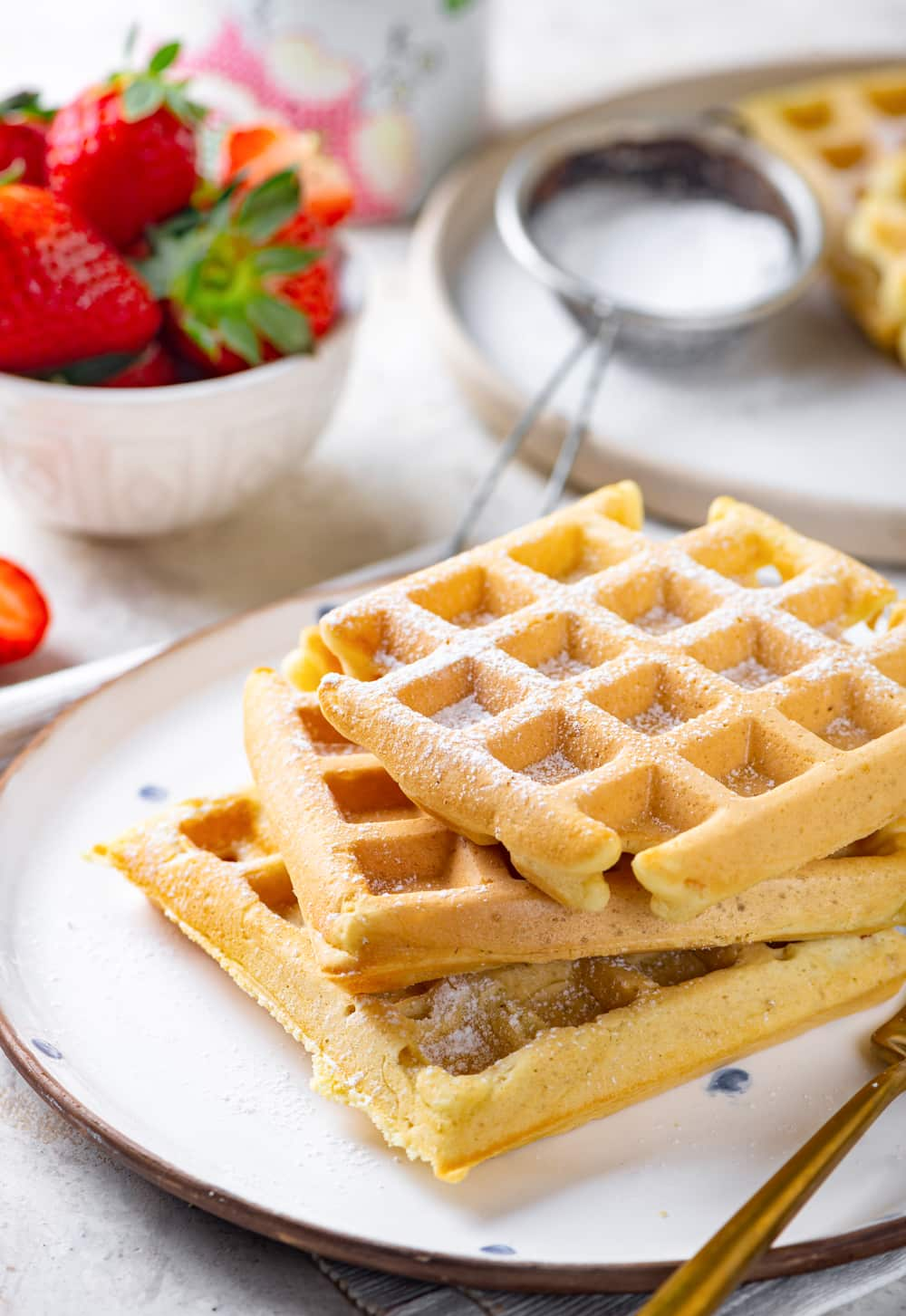A stack of three square vegan waffles with powdered sugar on top. The waffles are on a white plate and there is a small white bowl of strawberries behind the plate to the left with a sifter of powdered sugar to the right.