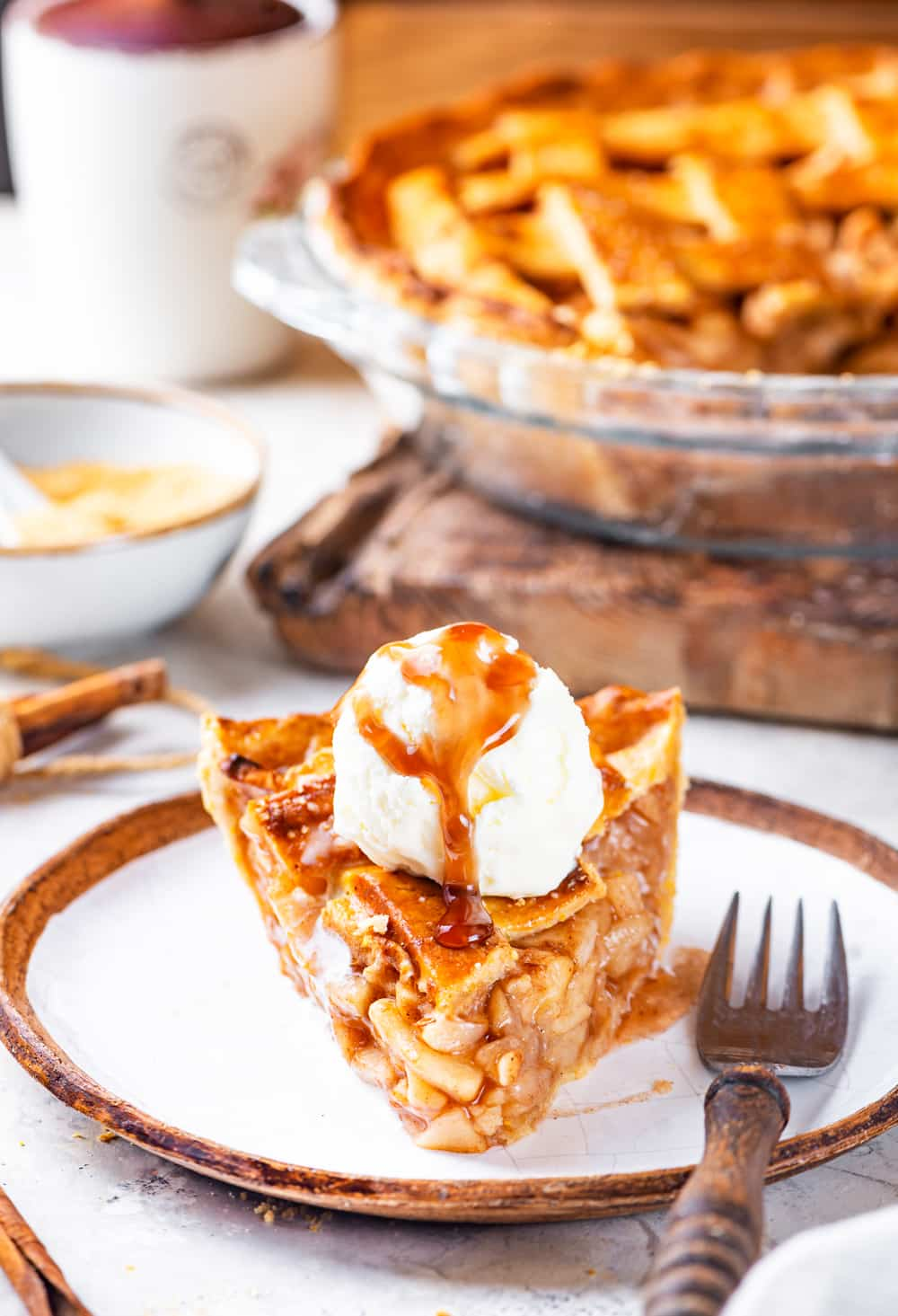 A front view of a piece of apple pie with a scoop of vanilla ice cream on top with a caramel sauce drizzled over it. The piece of pie is on a white plate and a fork is to the right of the piece of pie. A vegan apple pie in a glass pie dish on a wooden cutting board is behind the plate. A cup of coffee is to the left of the pie. It is all set on a grey counter.