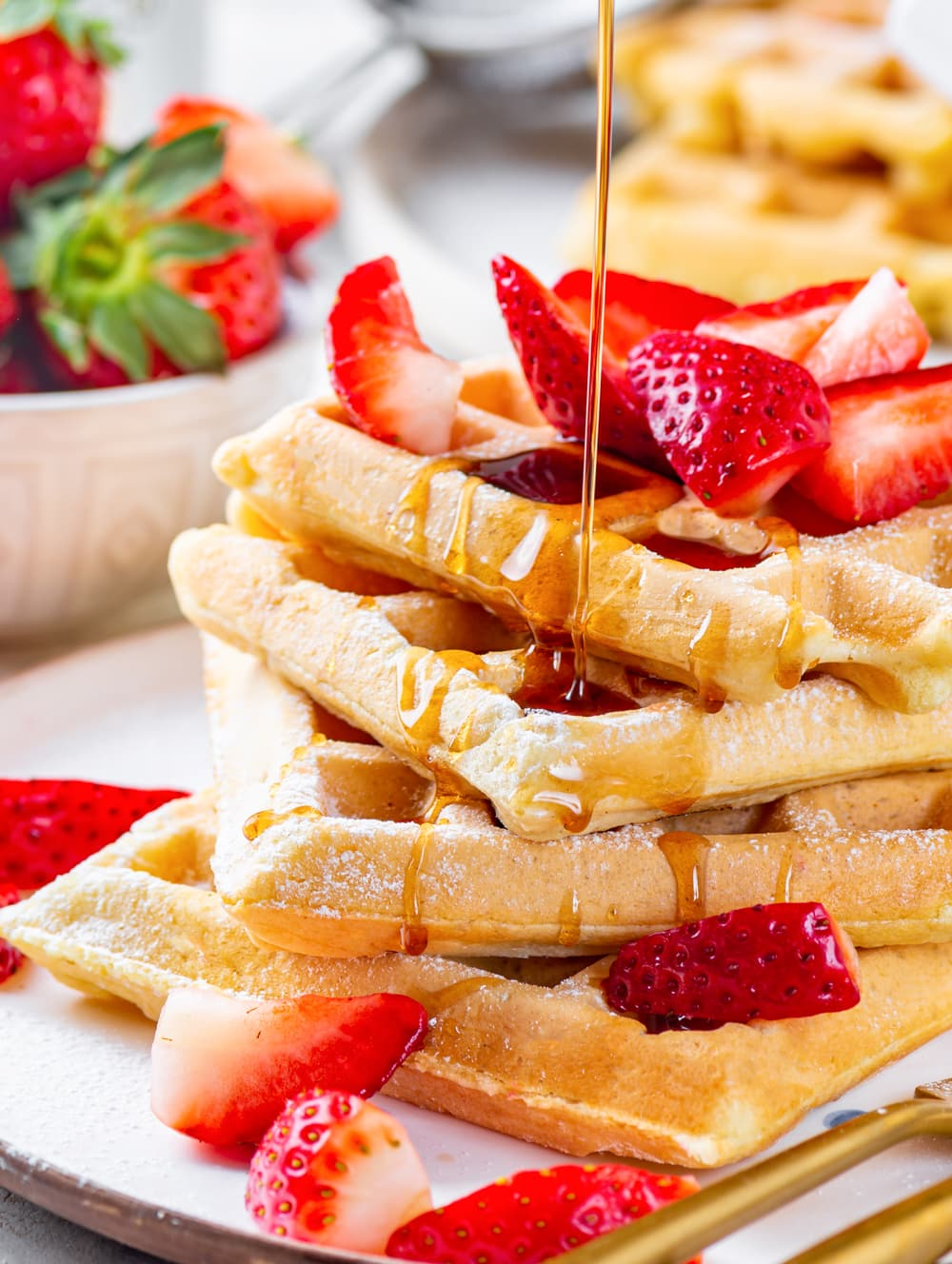 Four square vegan waffles unevenly stacked on top of one another with strawberries on them. Maple syrup is being poured on the waffles from the top. Part of a white bowl of strawberries and two vegan waffles are in the background.