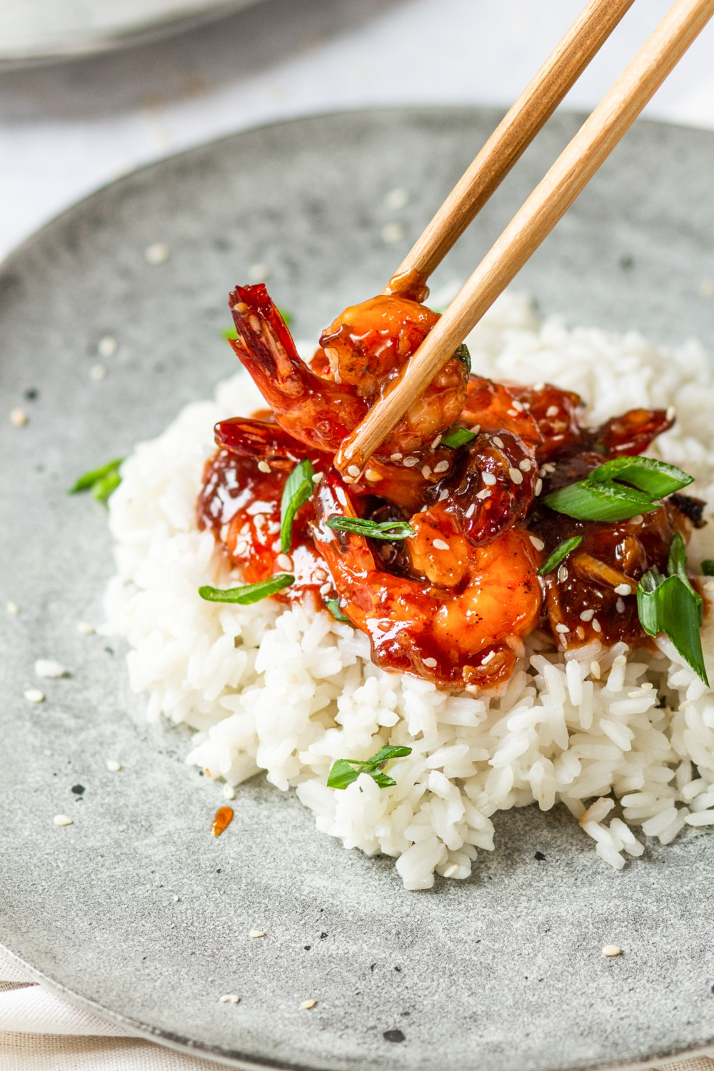 A few pieces of sweet and sour shrimp on a bed of white rice on a grey plate. A pair of chopsticks are grabbing a piece of shrimp from the pile of shrimp. Sesame seeds and sliced green onion are on top of the shrimp.