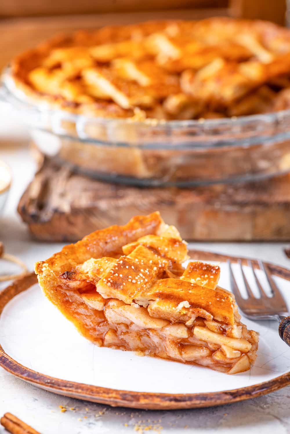 A side view of a piece fo apple pie on a white plate. A fork is to the right of the piece of pie. The entire vegan apple pie minus the one piece is behind the plate. The vegan apple pie is in a glass pie plate on top of a wooden cutting board. Everything is on a grey counter.