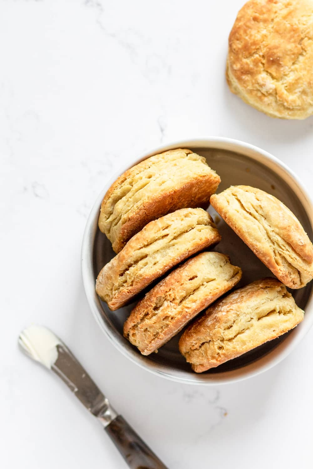 An overhead view of five vegan biscuits on their side in a white bowl. There is a knife with butter on it in front of the bowl. A vegan biscuit is behind the bowl. Everything is on a white counter.