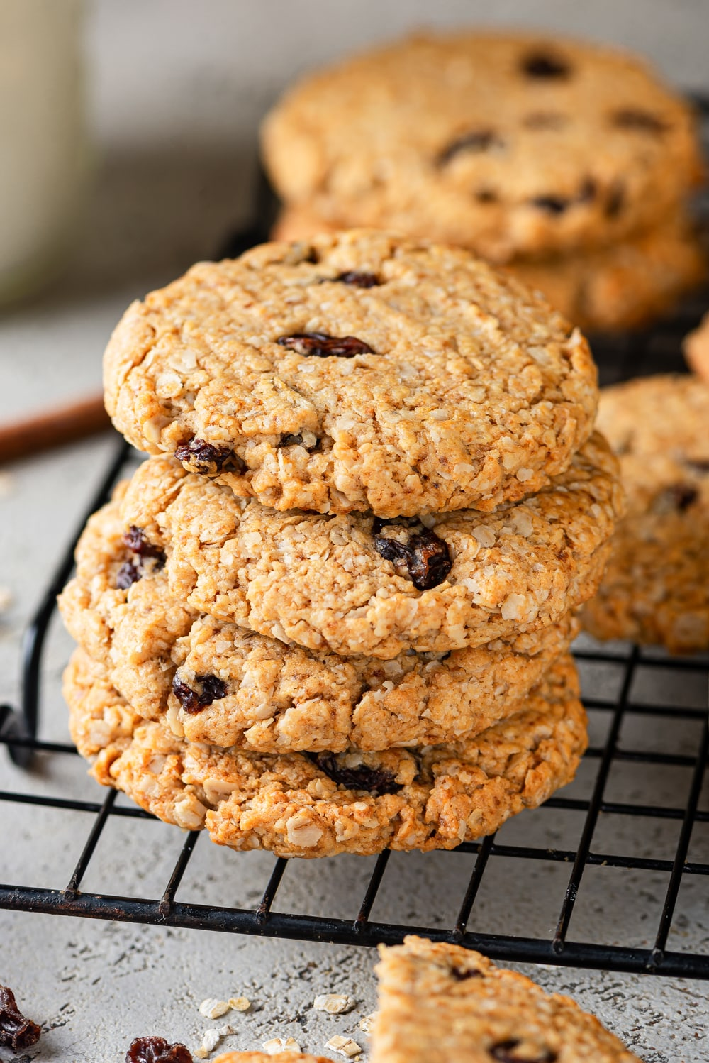 A stack of four vegan oatmeal raisin cookies on top of a black wire rack. A smaller stack of two cookies is behind the stack of four and one cookie is in the middle of the two stacks, slightly to the right. The wire rack is on a grey counter.