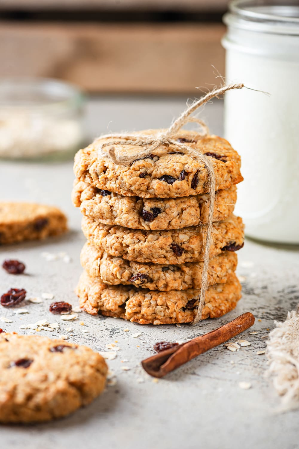 Five vegan oatmeal raisin cookies stacked on top of each other with a yarn rope wrapped around the cookies on both sides and tied in a knot on top, on the top cookie. A glass jar of milk is set behind the cookies to the right and a half a cookie is to the left behind the stack and the other half is in front of the stack. A cinnamon stick is directly in front of the stack of cookies and everything is on a grey counter.