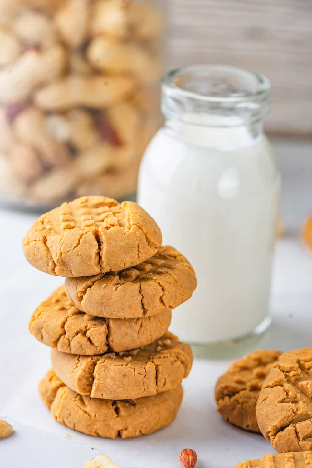 An offset stack of five vegan peanut butter cookies. There are two cookies overlapping each other to the right of the stack of cookies. A tall glass jar of milk is set behind the stack of cookies. A glass jar of peanuts is in the back behind everything. Everything is set on a white counter.