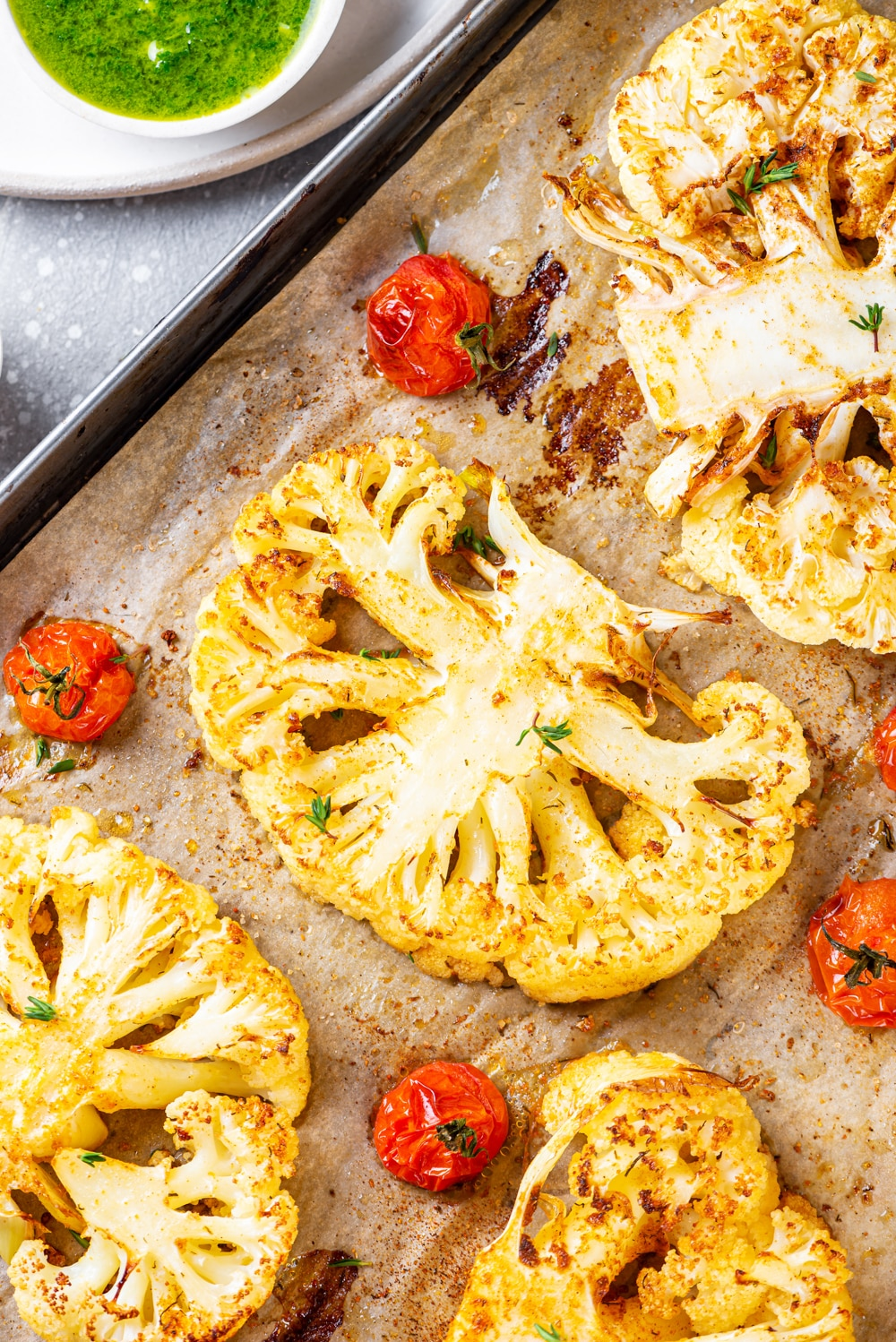 A close up view of one whole cauliflower steak with a half of a cauliflower steak on each side of it. There are four cherry tomatoes spaced evenly around the steaks. Everything is on a baking sheet lined with parchment paper.