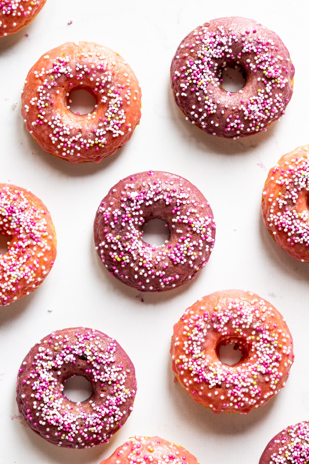 An overhead view of five whole vegan donuts with four halves of vegan donuts on the sides. The donuts all have a pink glaze with white, pink, and yellow ball sprinkles on top.