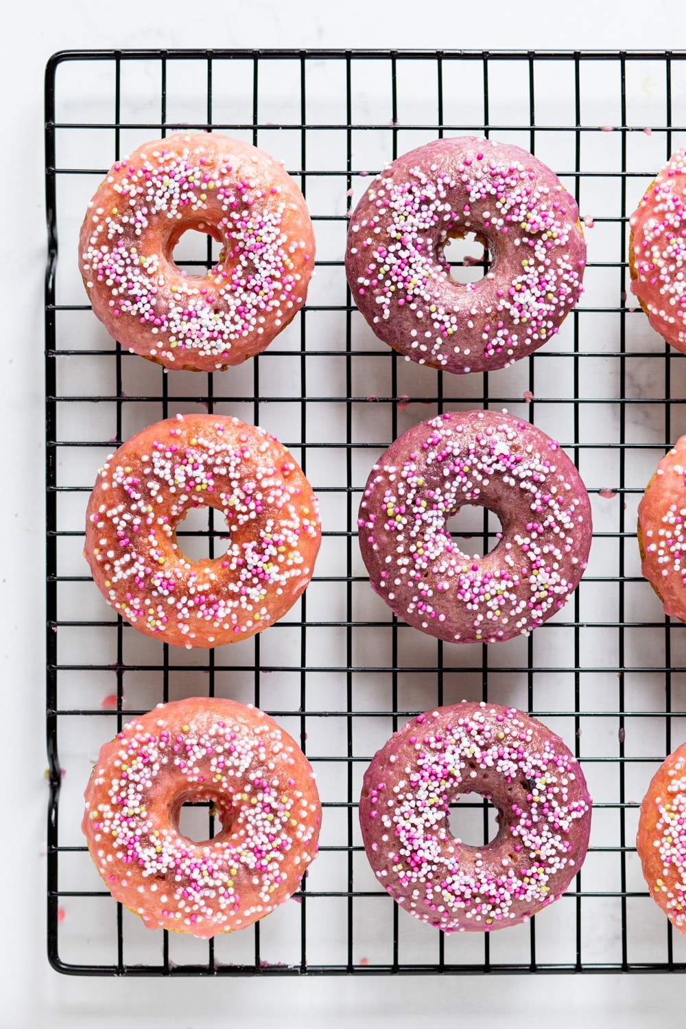 An overhead view of two rows of vegan donuts with three donuts in each row on a black wire rack. There is pink glaze with white, pink, and yellow ball sprinkles on top.