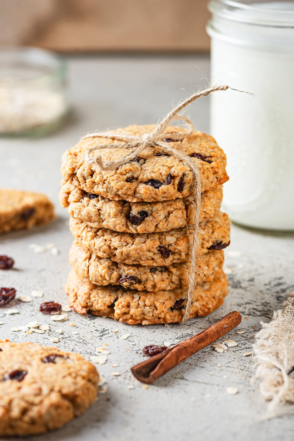 Five vegan oatmeal raisin cookies stacked on top of one another with a piece of yarn tied around the cookies. A glass jar of milk is behind the cookies to the right and a cinnamon stick is directly in front of the cookies. A half of a cookie is to the left of the cinnamon stick and everything is on a grey counter.