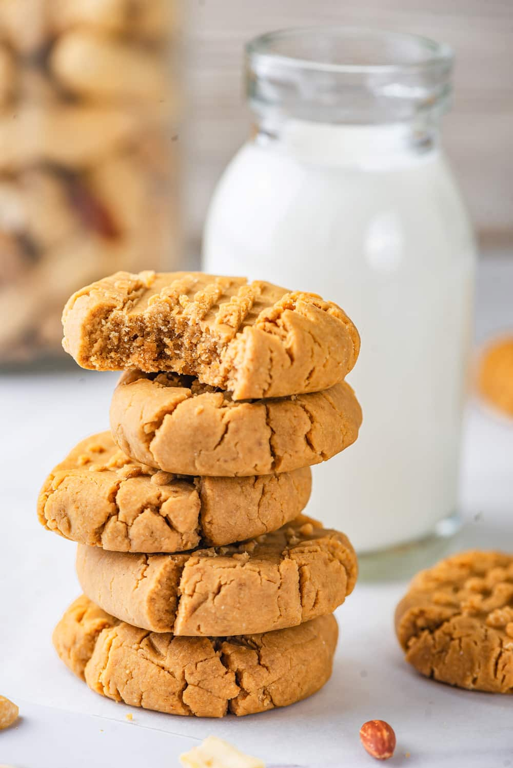 A stack of five vegan peanut butter cookies. There is a bite out of the top cookie with the inside of the cookie showing. A tall glass jar of milk is right behind the stack of cookies and there is one cookie to the right of the stack. The cookies and milk are set on a white counter.