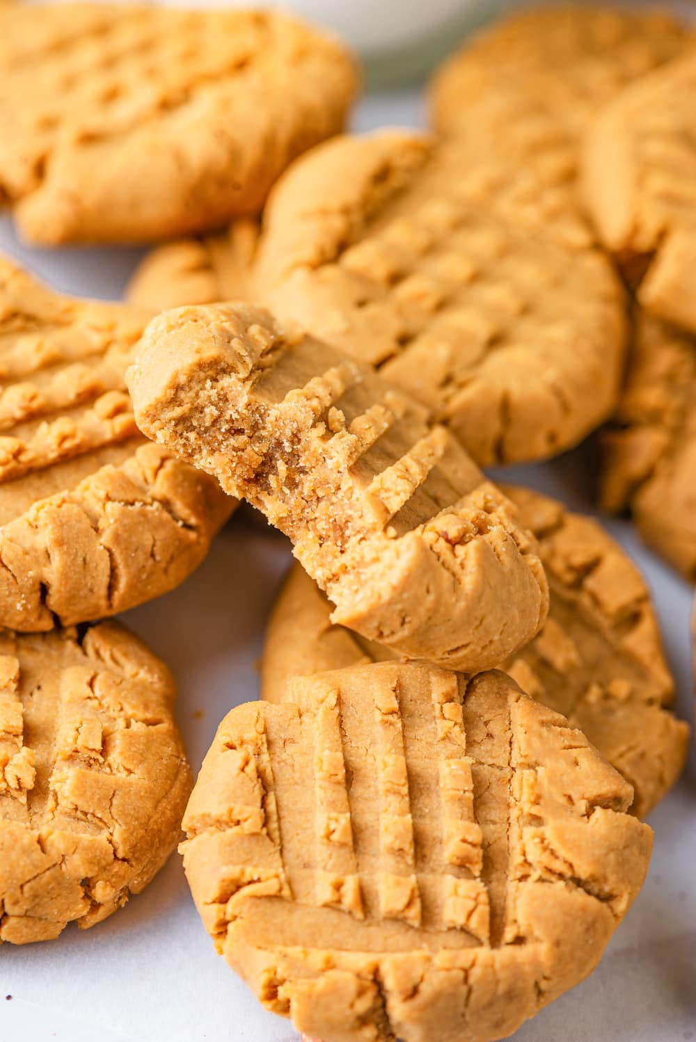A bunch of vegan peanut butter cookies scattered overlapping one another. One cookie with a bite out of it is at the front set on top of the other cookies. The inside of the bitten cookie is showing. All of the cookies are on a white counter.