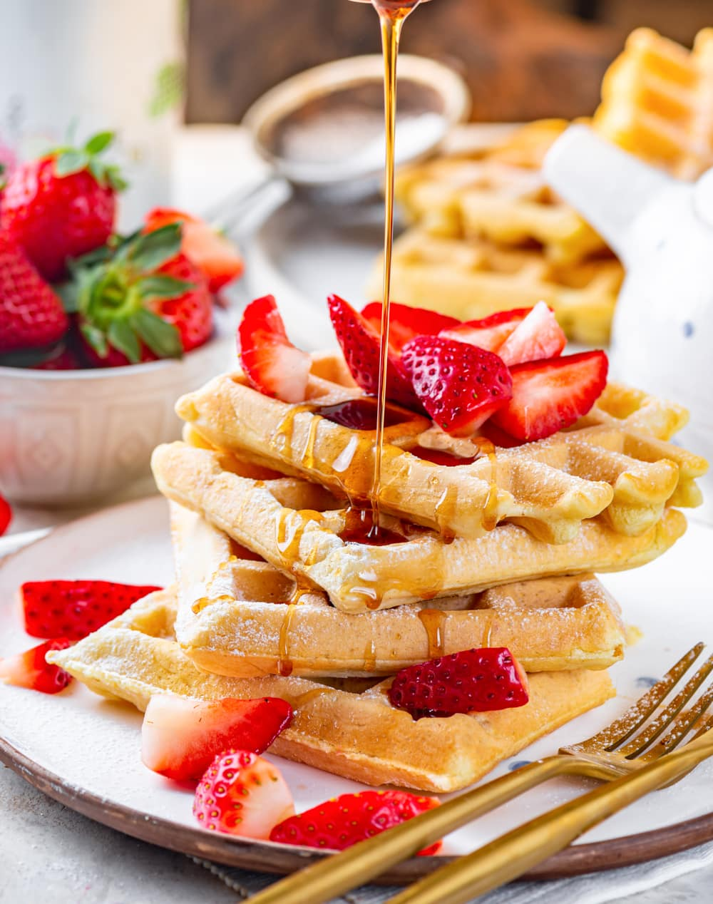 Four square vegan waffles stacked unevenly on a white plate. There are cut up strawberries on the waffles and maple syrup being poured on top. A gold fork is at the front of the plate and there is a bowl of strawberries at the back left of the plate and a plate of vegan waffles directly behind the plate.