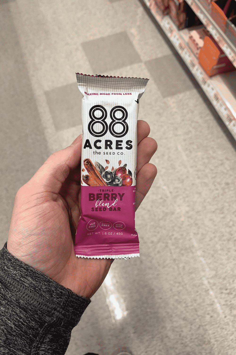 A hand holding a wrapped 88 Acres triple berry blend seed bar.