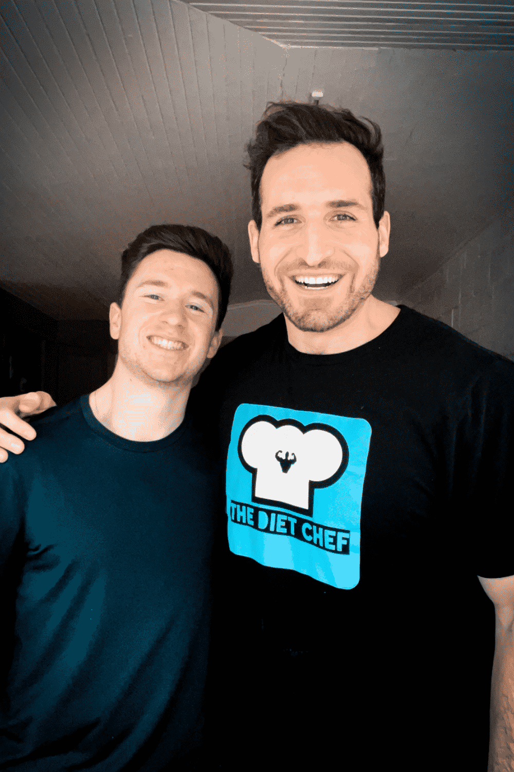 Two men in a kitchen smiling.