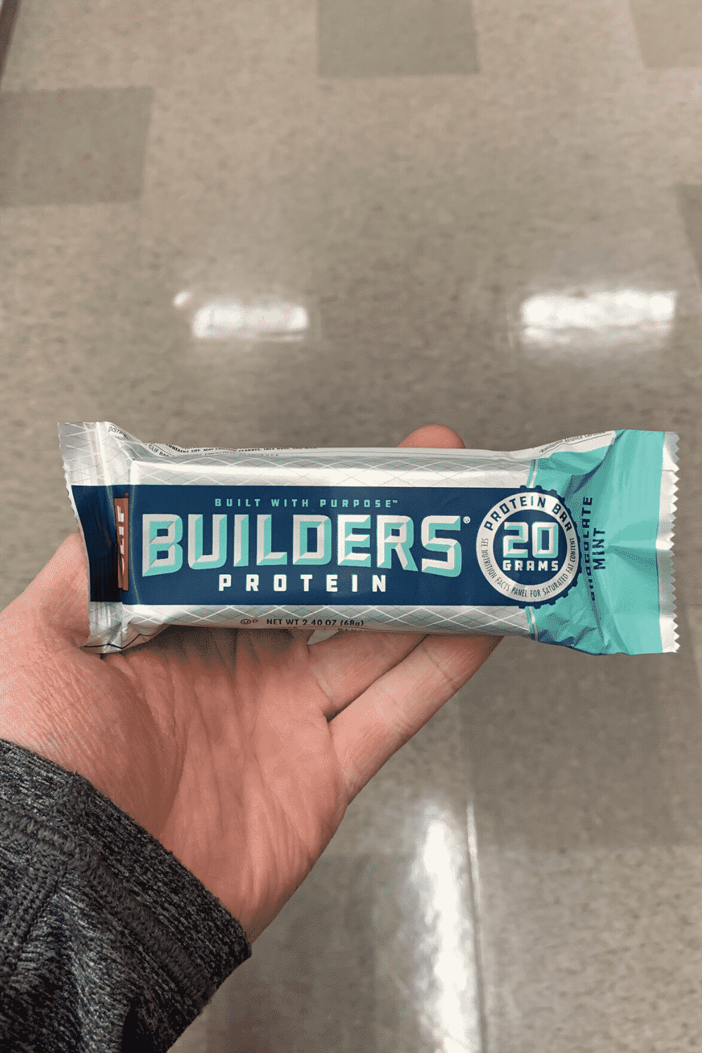 A hand holding a wrapped Clif builders bar mint chocolate flavored.