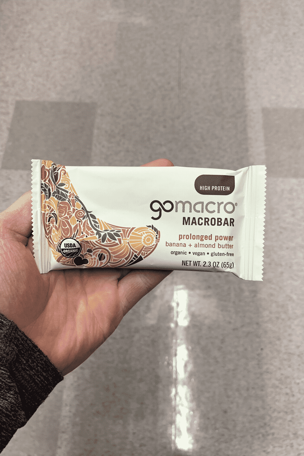 A hand holding a wrapped gomacro banana plus almond butter flavored bar