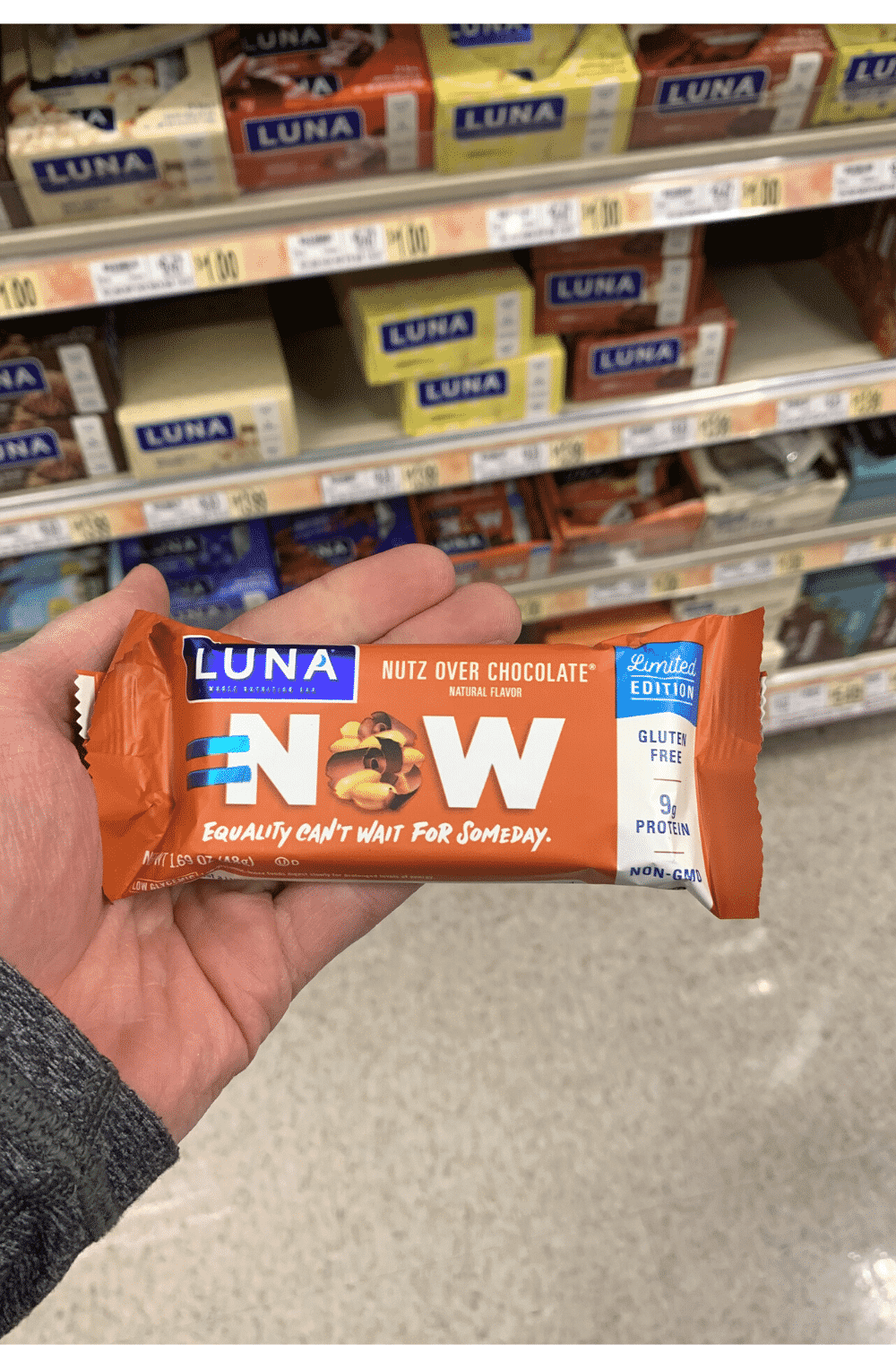 A hand holding a wrapped Luna nutz over chocolate flavored bar