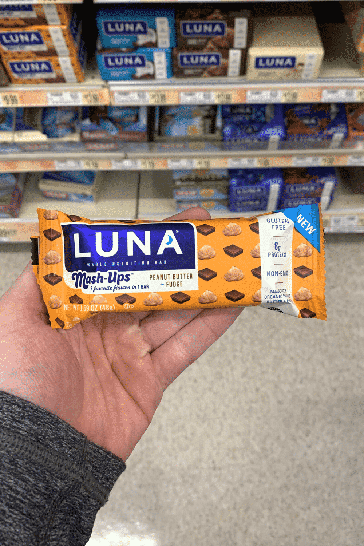 A hand holding a wrapped Luna mash-ups peanut butter plus fudge bar.
