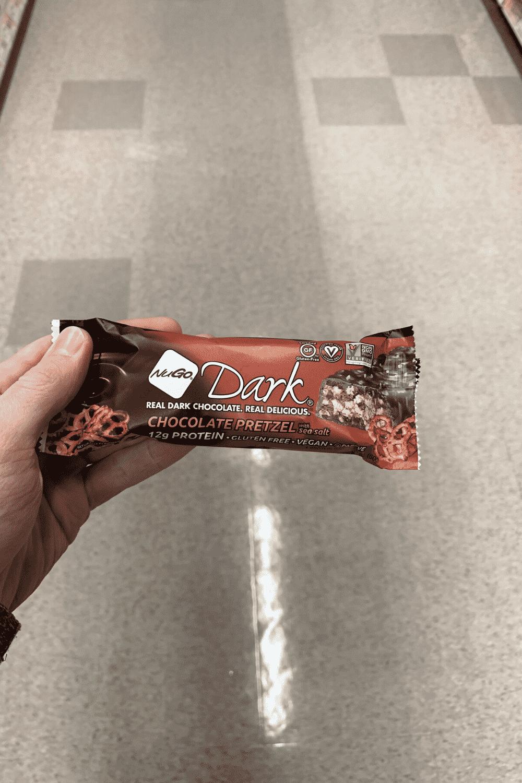 A hand holding a wrapped nugo dark chocolate pretzel bar.