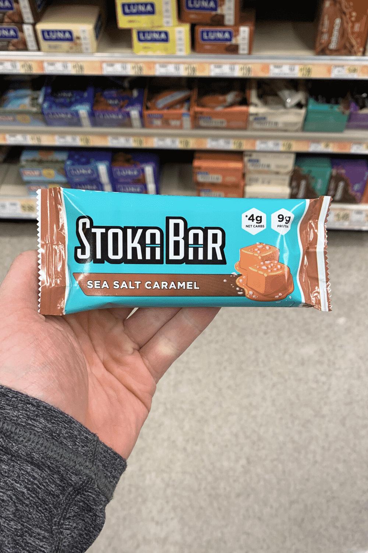 A hand holding a wrapped sea salt caramel flavored Stoka bar