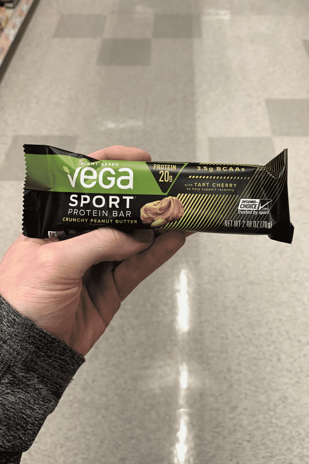 A hand holding a wrapped crunchy peanut butter vega sport protein bar
