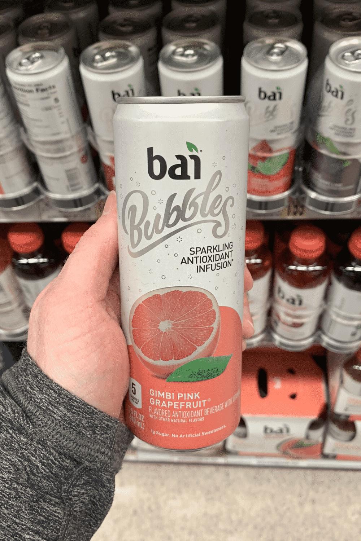 A hand holding a can of gimbi pink grapefruit bai bubbles.