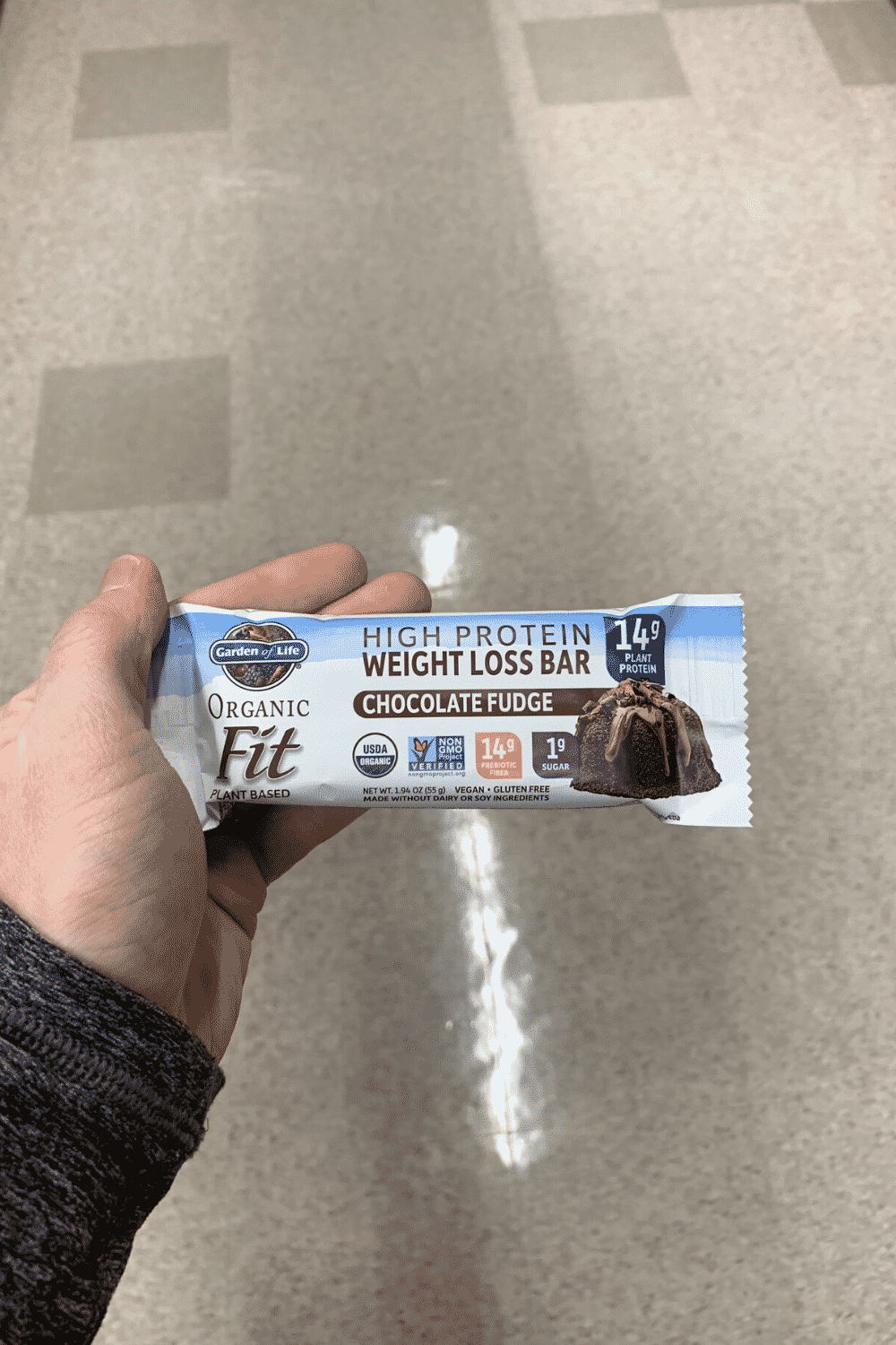 A hand holding a wrapped chocolate fudge garden of life high protein fat loss bar