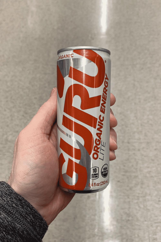 A hand holding a can of Guru lite organic energy drink