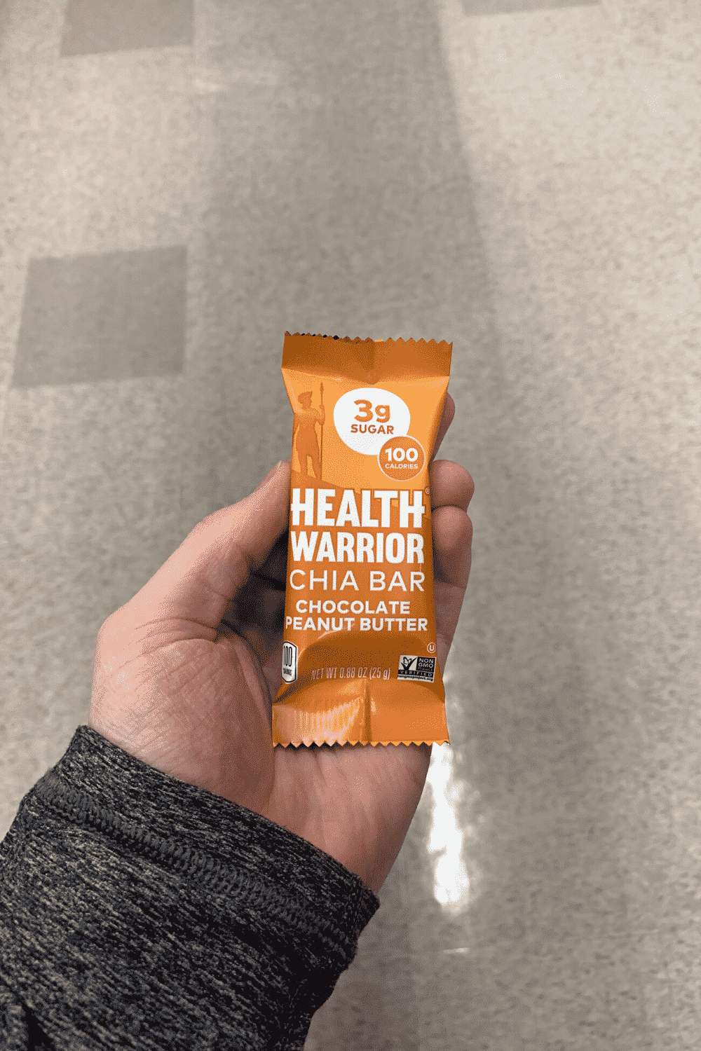 A hand holding a wrapped chocolate peanut butter Health Warrior Chia Bar