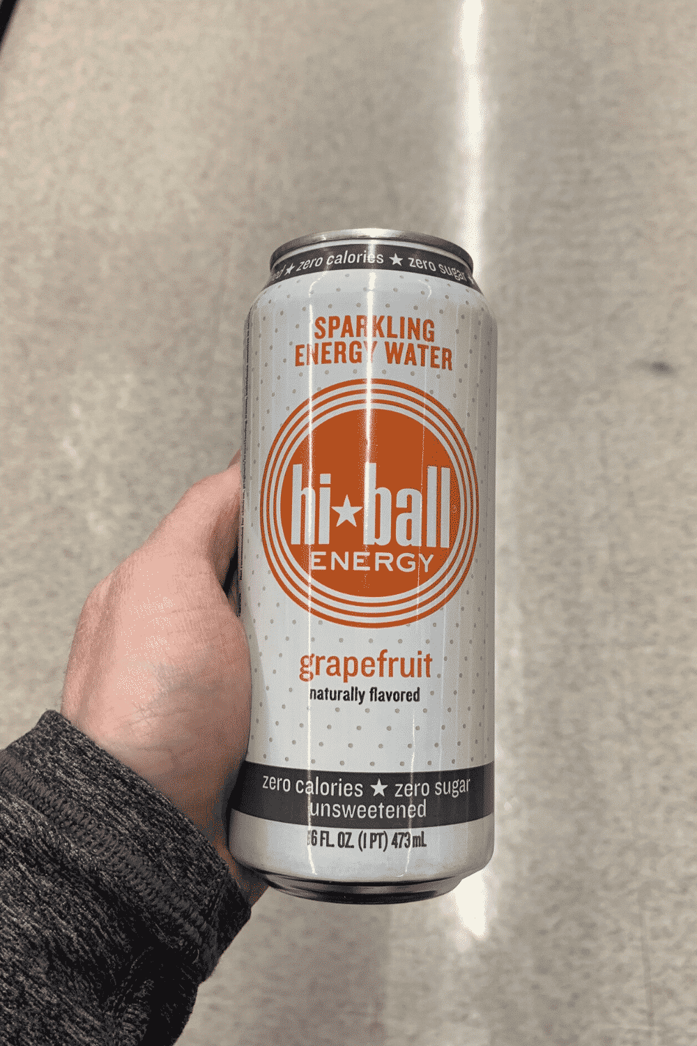 A hand holding a can of hi-ball energy drink grapefruit flavored