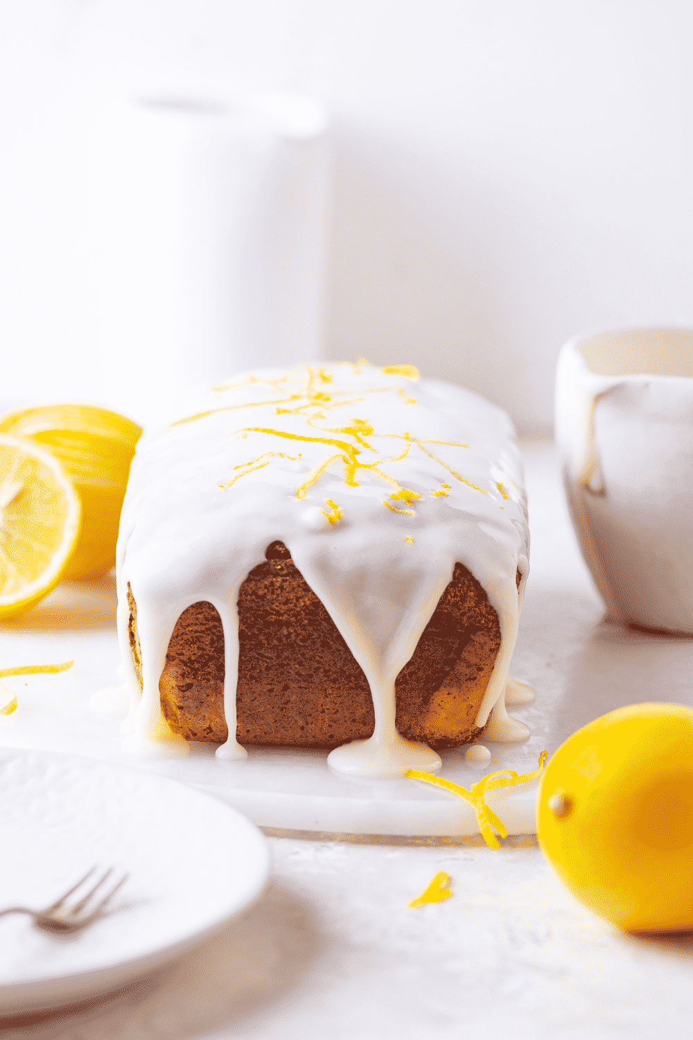 A loaf of keto lemon pound cake on a white round cutting board. There are a few lemons around the cake. A white plate with a fork on it is in front of the keto cake.