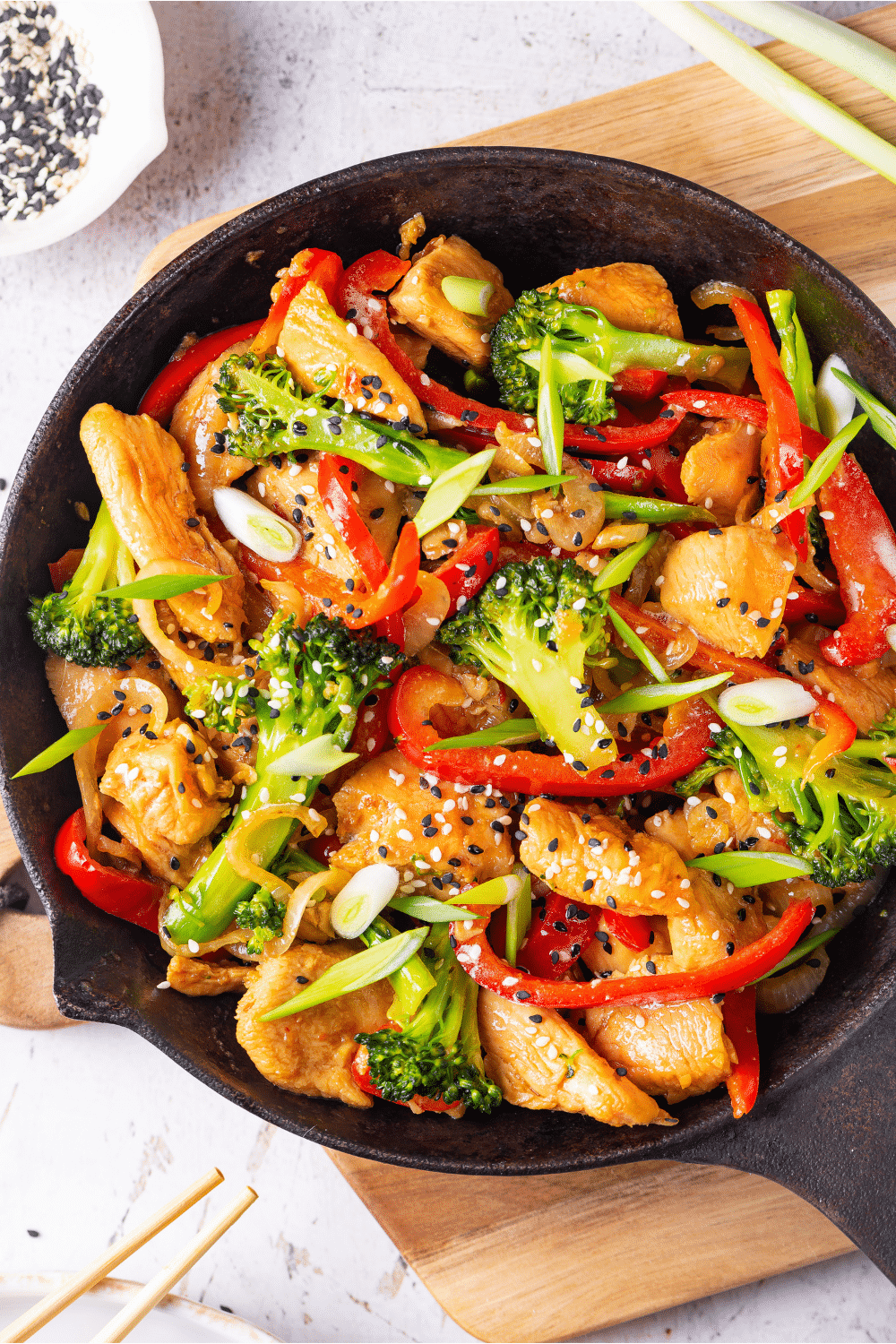 A skillet filled with keto chicken stir fry. The skillet has broccoli, red peppers, chicken, and onions in it covered in a keto stir fry sauce. The skillet is on a wooden cutting board on a white table.