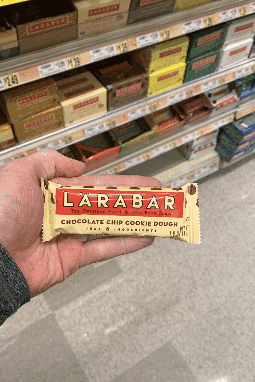 A hand holding a wrapped chocolate chip cookie dough larabar.
