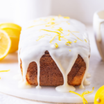 A loaf of keto lemon pound cake with keto glaze dripping down the side front of the cake. There is a lemon zest on top of the white glaze. The low carb lemon pound cake is on a white saucer on a white table.