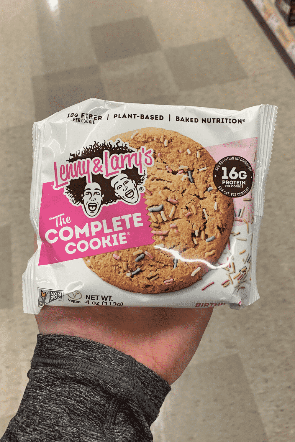 A hand holding a wrapped Lenny and Larry's Complete Cookie birthday cake flavor.