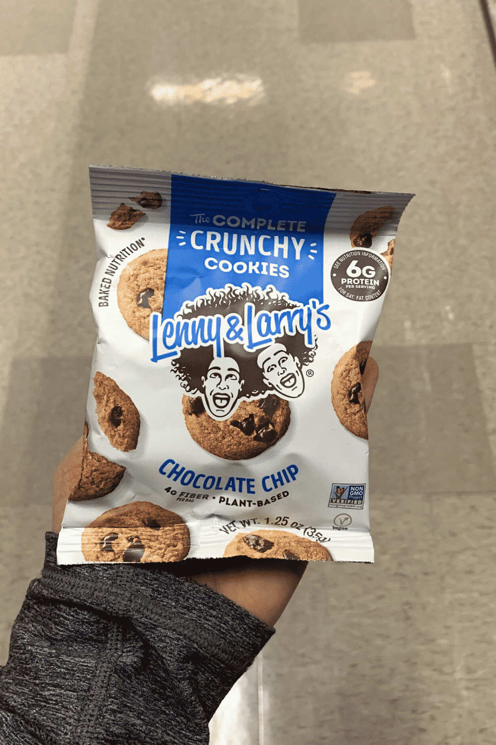 A hand holding a bag of Lenny and Larry's crunchy chocolate chip cookies