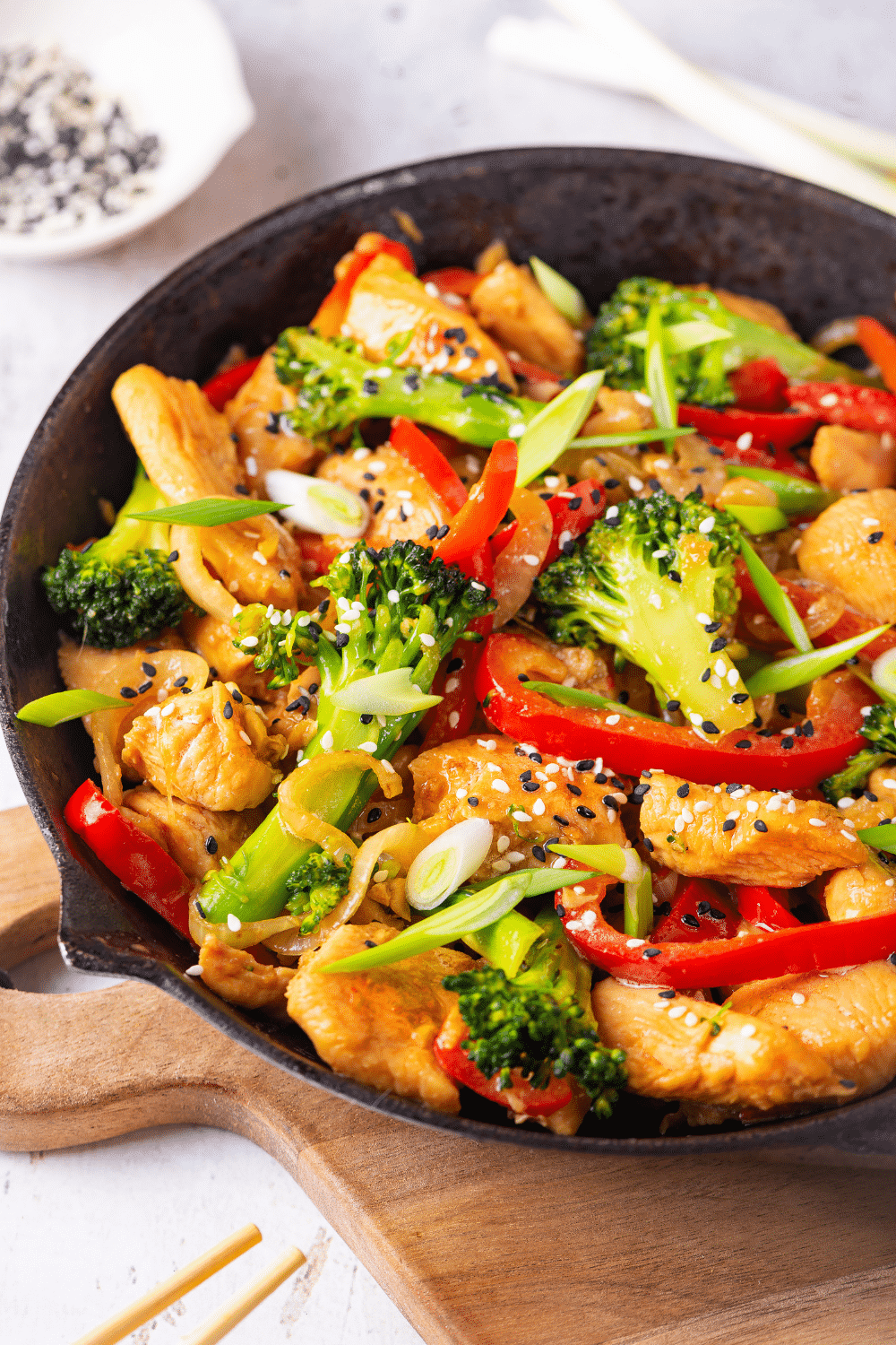 A skillet filled with keto stir fry. The skillet has chicken, broccoli, red peppers, and onions in it. Everything is covered in a keto stir fry sauce. The skillet is on a wooden cutting board on a white counter.