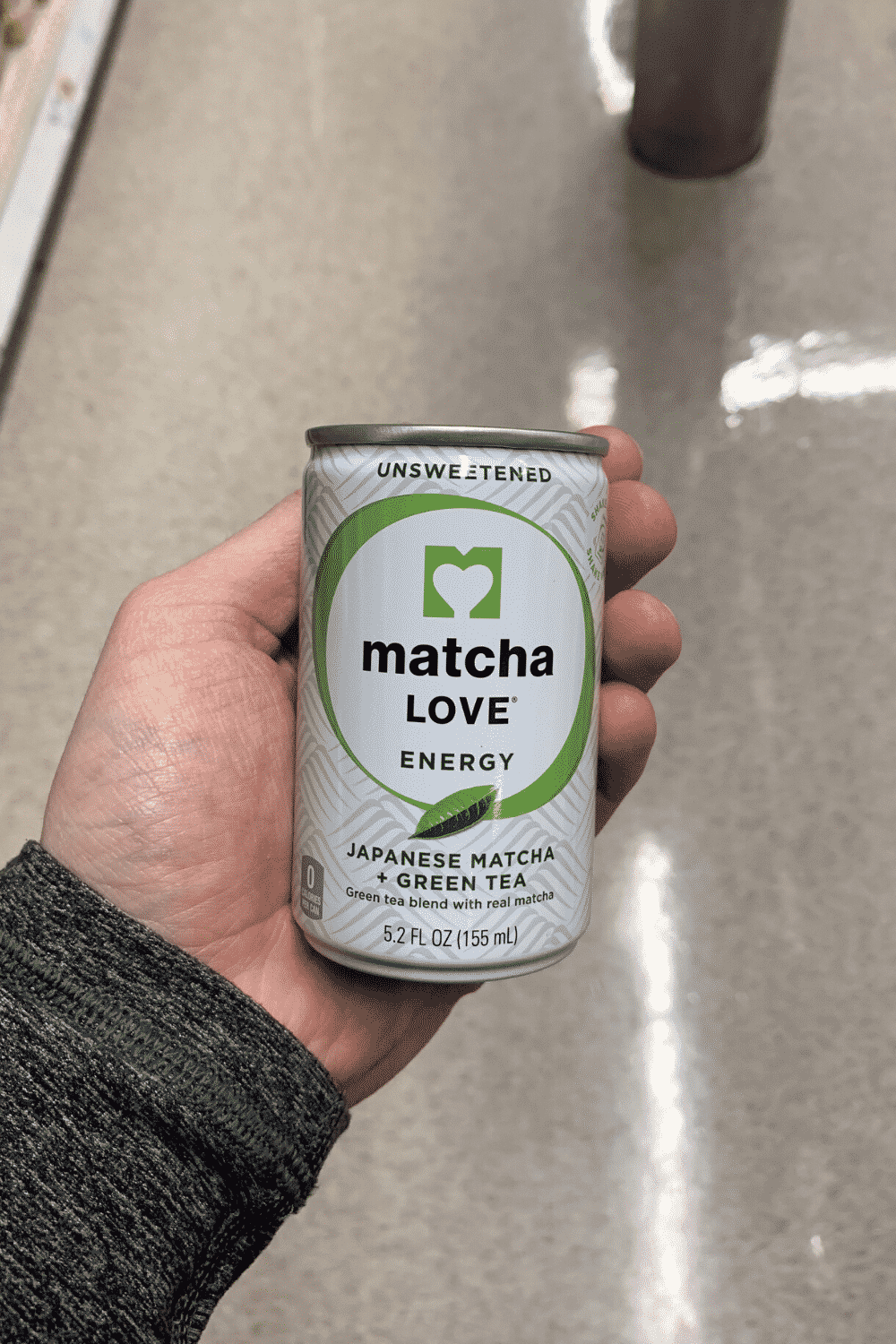 A hand holding a can of unsweetened matcha love energy.