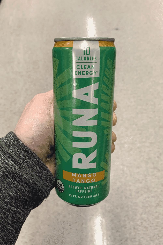 A hand holding a can of Runa mango tango falvor