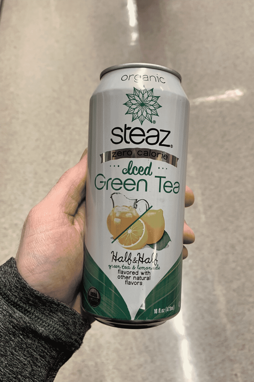 A hand holding a can of zero calories Steaz iced green tea
