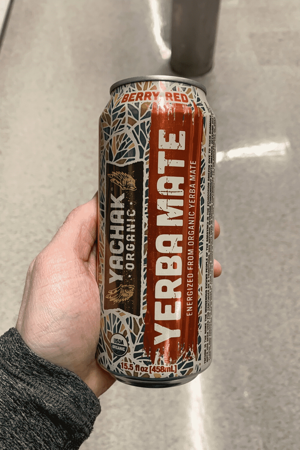 A hand holding a can of yachak organic year mate.
